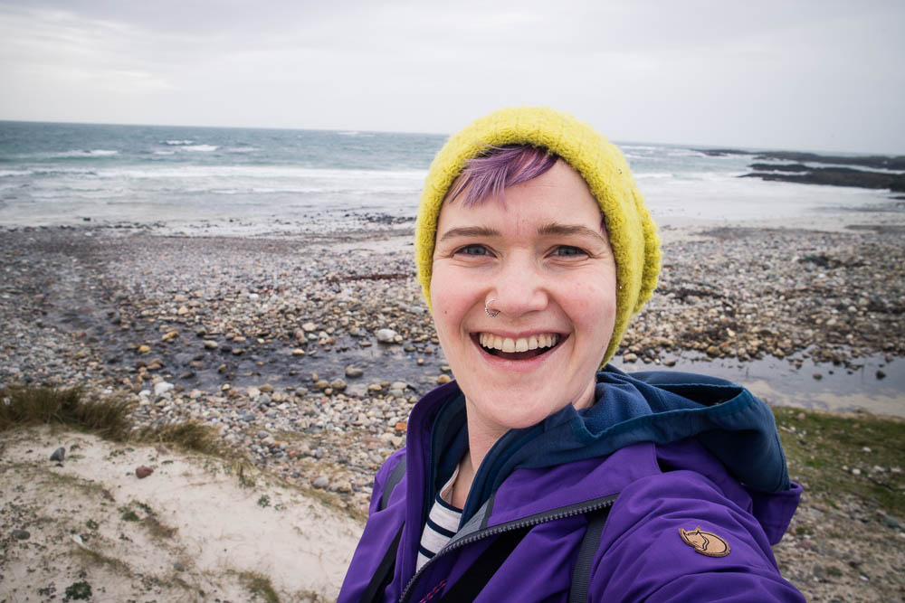 A selfie of a woman in purple jacket and yellow hat by a beach.