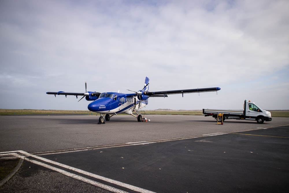 Small blue Loganair plane on the air strip.