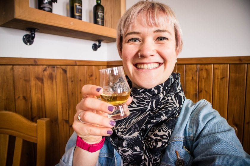 a woman holding a glass of whisky, selfie