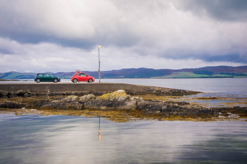 Two cars standing on line at a ferry jetty by the sea