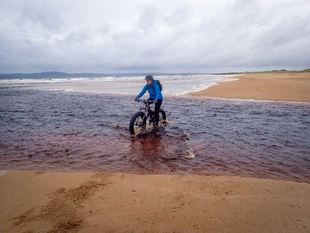 A woman fat biking on the beach