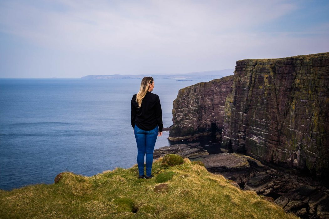 A woman standing by cliffs on Handa Island