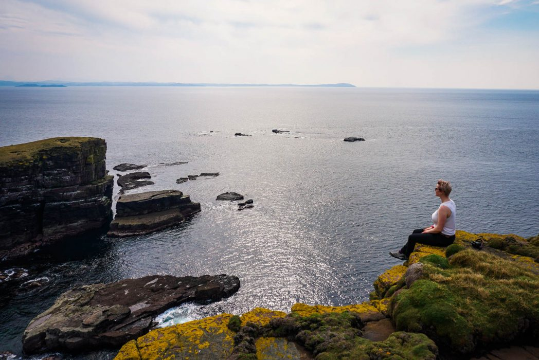 Woman sitting at the cliffs of Handa Island.
