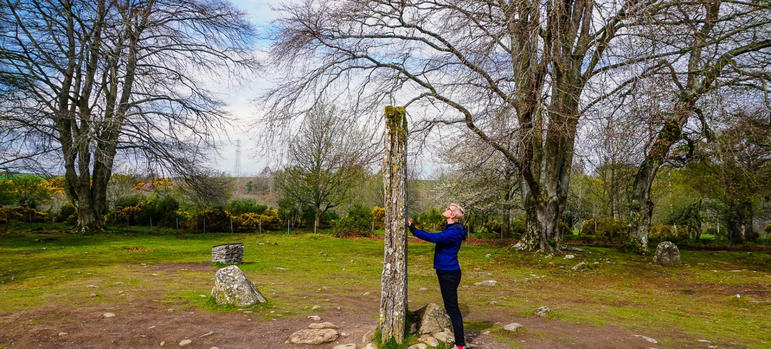 A woman standing in front of a standing stone in Scotland