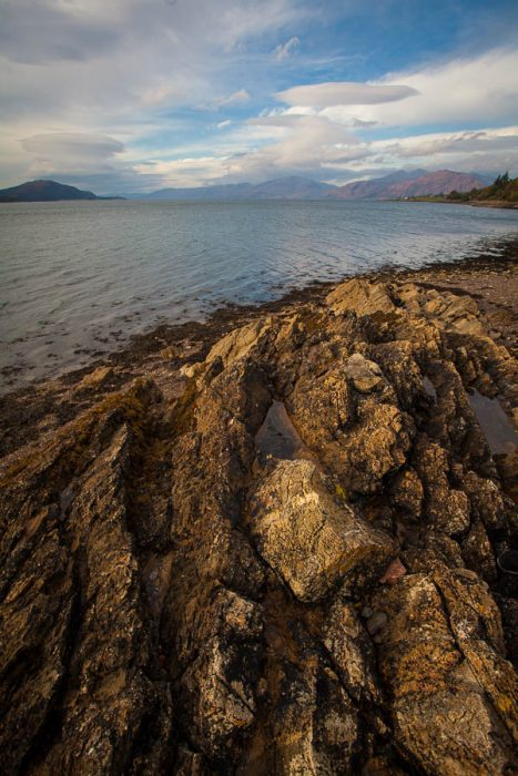 A rocky beach by a loch and mountains in the background.