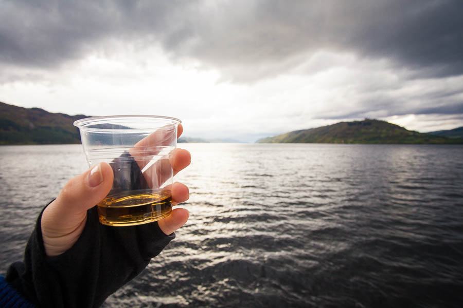 A hand holding a glass of whisky and Loch Ness in the background.