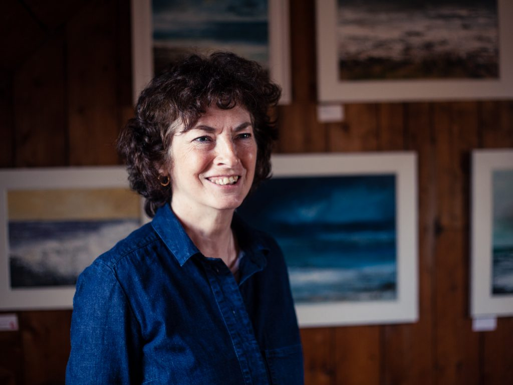 Seascape painter Frances Innes in front of her paintings.