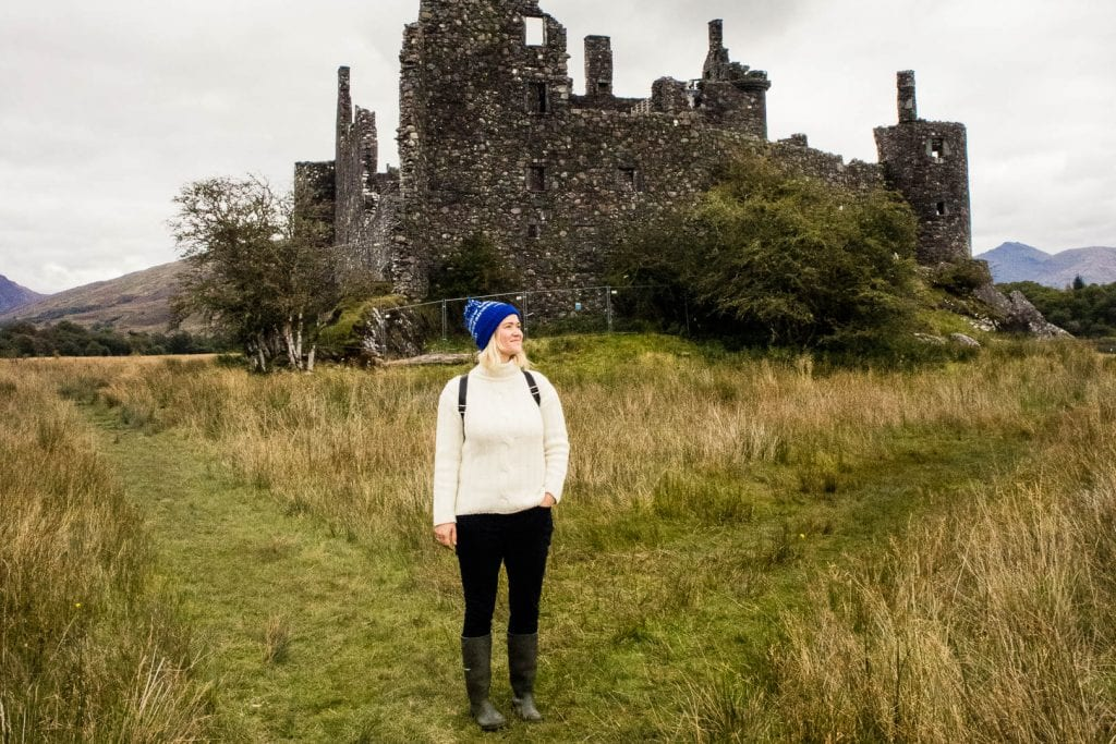 Girl in knitted jumper in front of a castle ruin in Scotland.