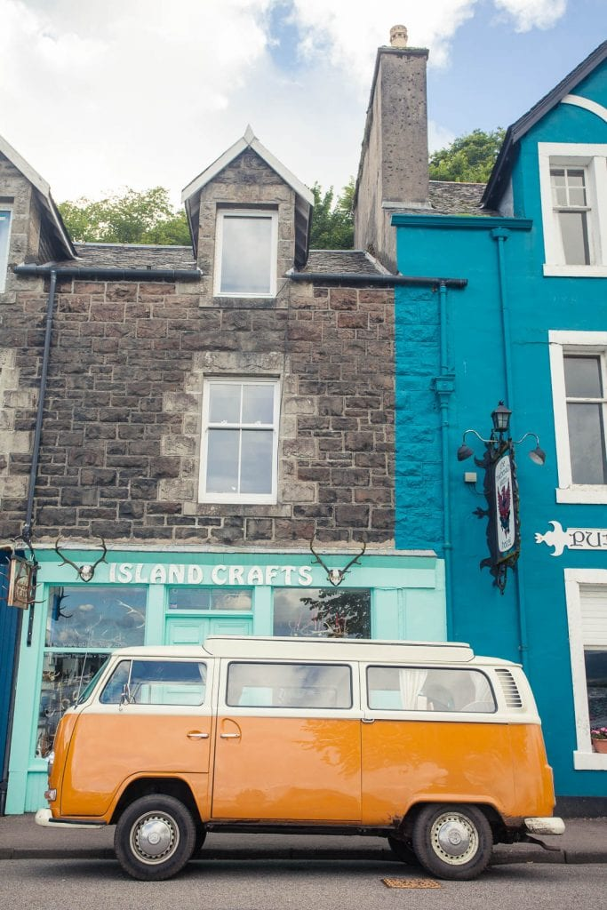 An orange VW bus in front of a colourful shop front in Tobermory.