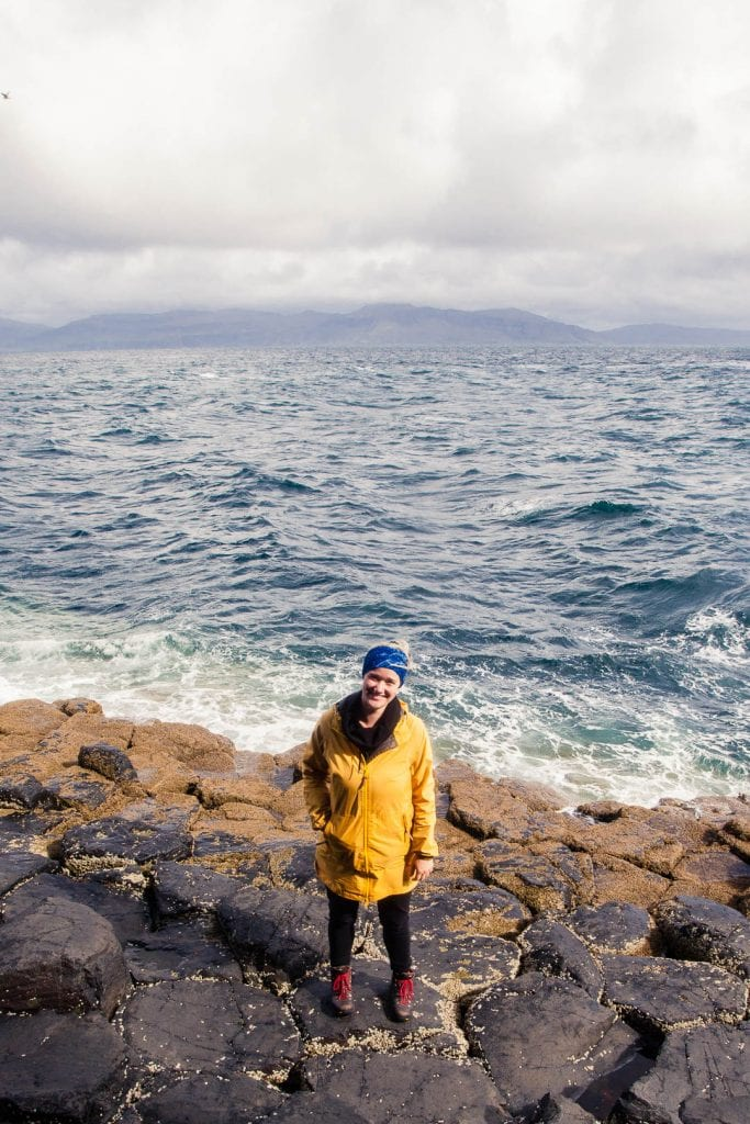 A woman in a yellow raincoat standing at the rocky shore of Staffa.
