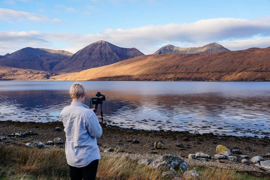 Woman taking photos of mountains on the Isle of Skye.