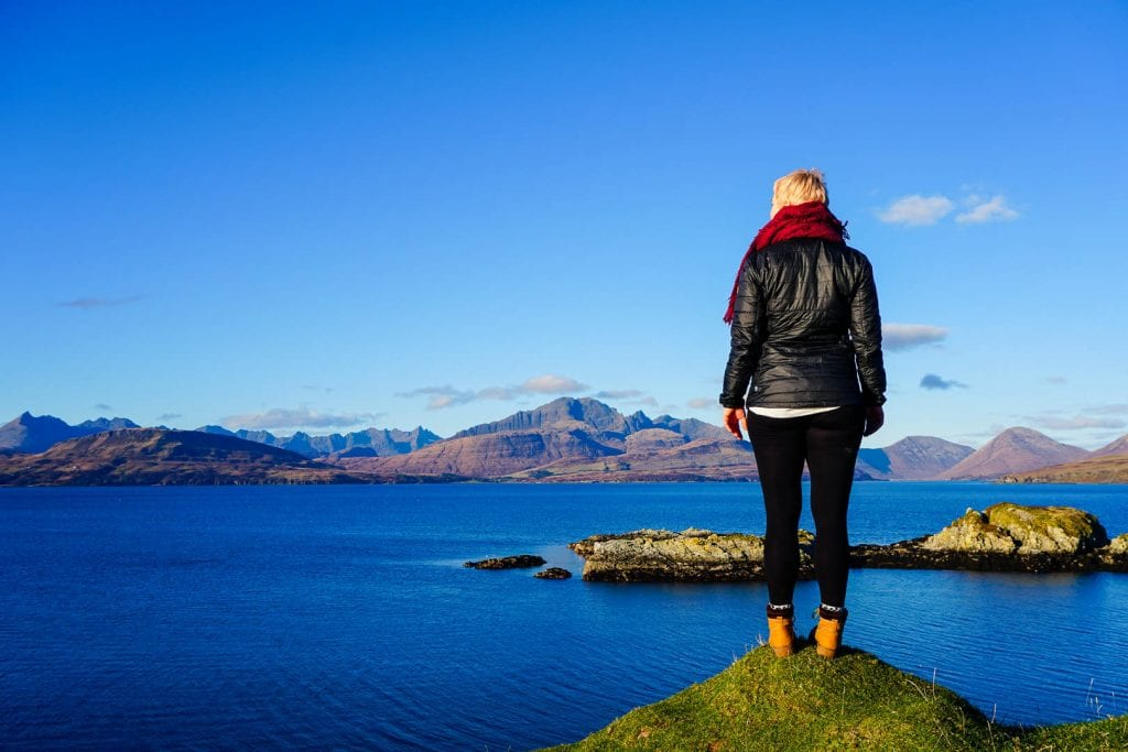 A woman standing at the Sleat Peninsula on Skye looking at the sea and mountains.