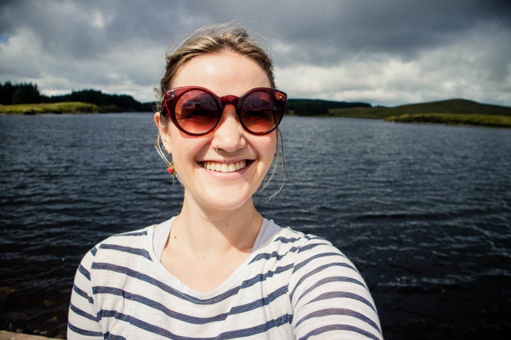 Travel blogger Kathi Kamleitner from Watch Me See, on a sunny day in the Kilpatrick Hills. Sunglasses and layers are essentials when packing for Scotland!