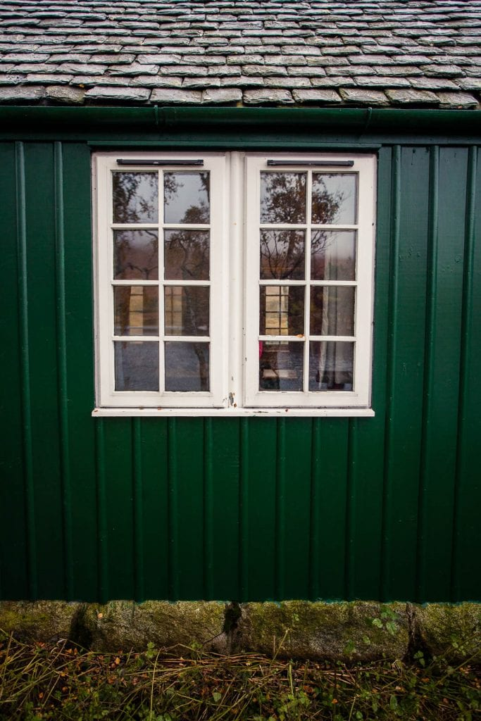 a window and green wall of Loch Ossian Youth Hostel
