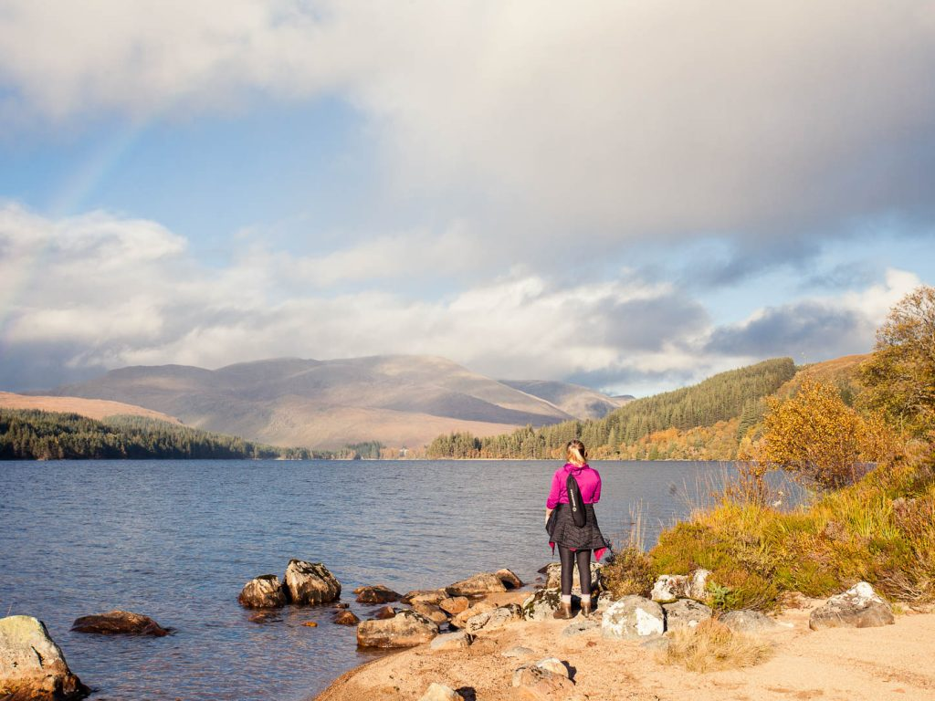 Woman standing by a lake and rainbow at Loch Ossian Youth Hostel