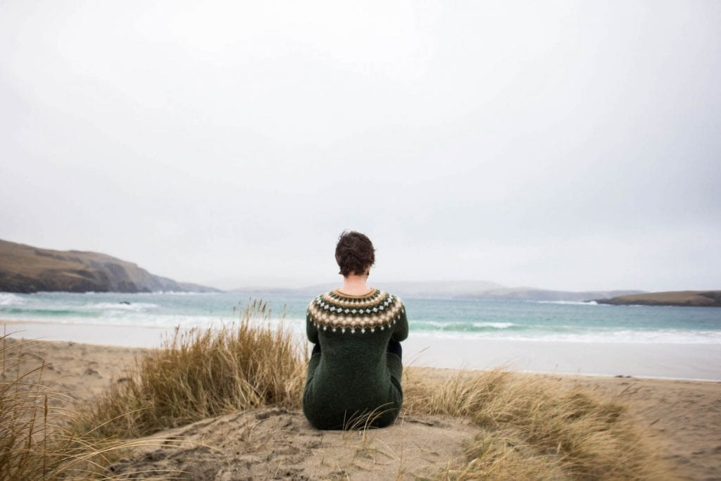 Girl sitting on a beach on Shetland in winter.