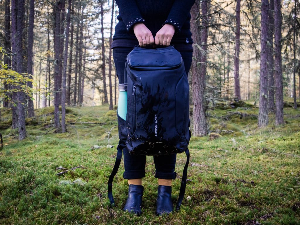 Woman holding a backpack in the forest