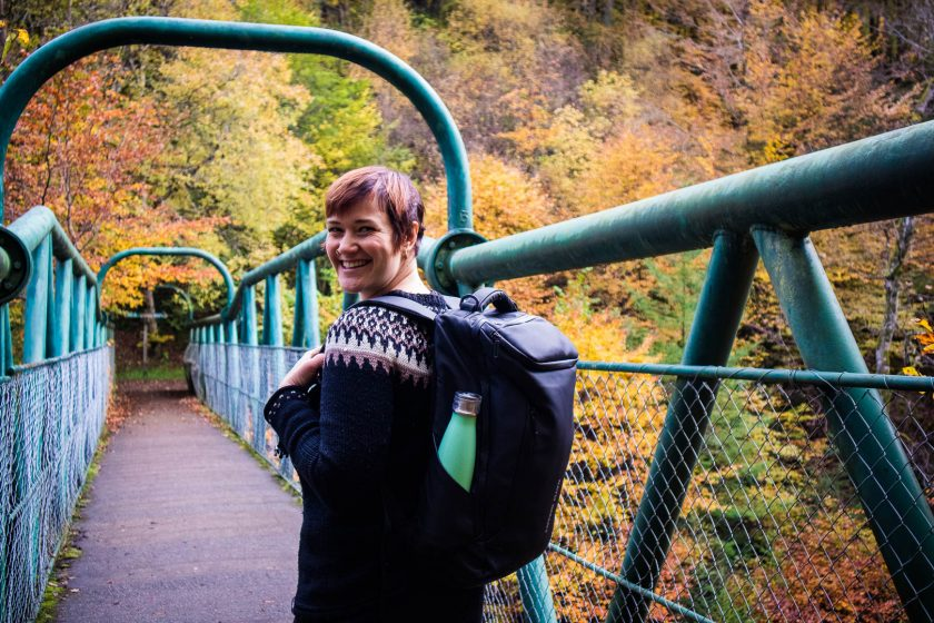 A woman wearing backpack, standing on a green bridge, turning around to the camera
