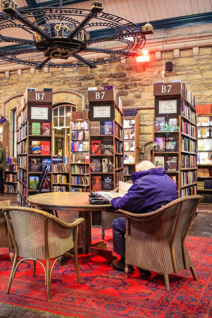 An old person sitting at a table in a book shop, Barter Books in Alnwick.