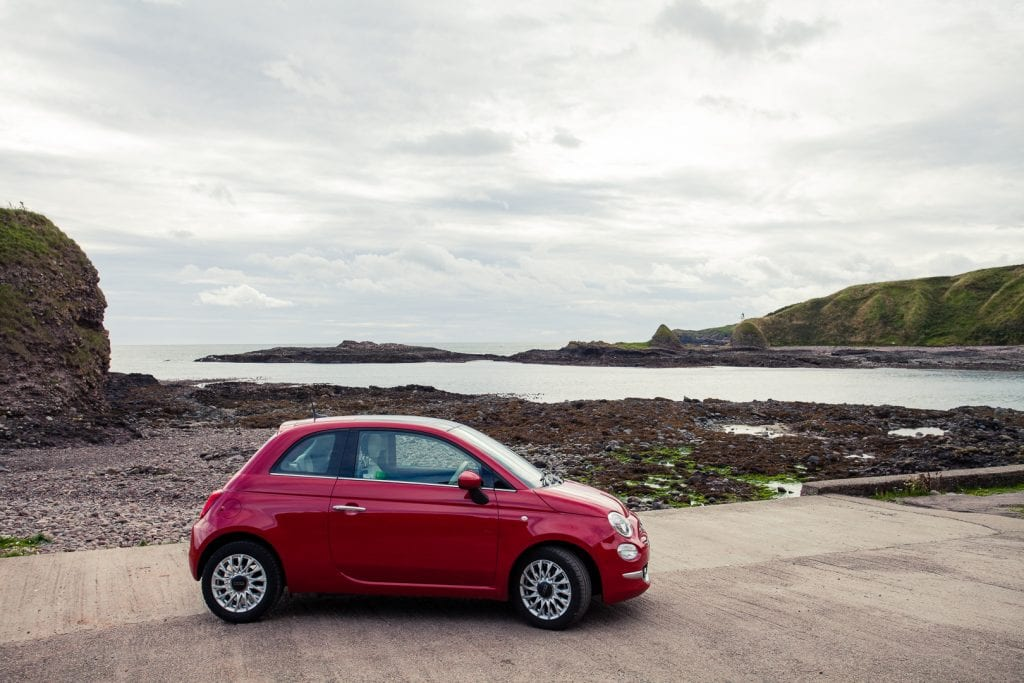 Small red car by the Scottish coast.