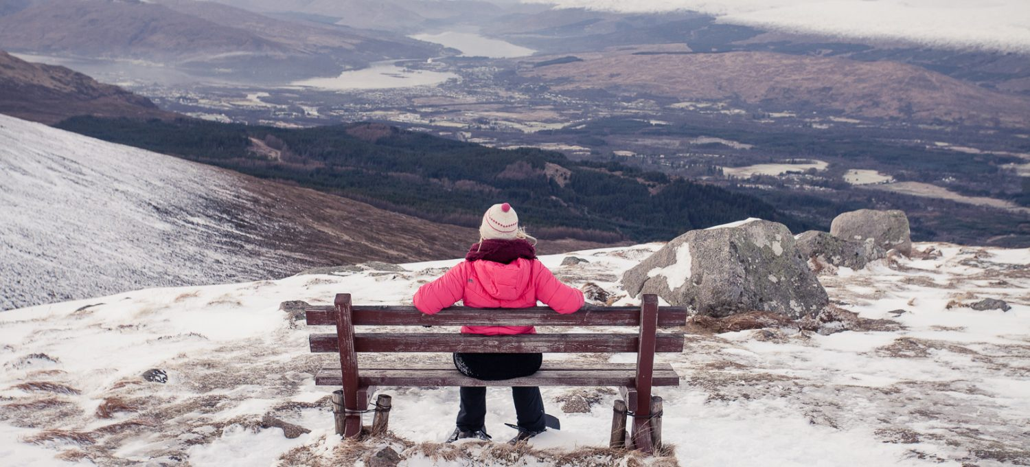 Girl in snowshoes sitting on a bench with mountain views.