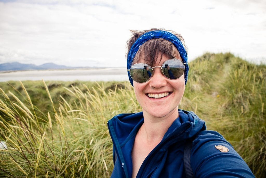 Girl taking a selfie in the dunes of Benbecula, Scotland
