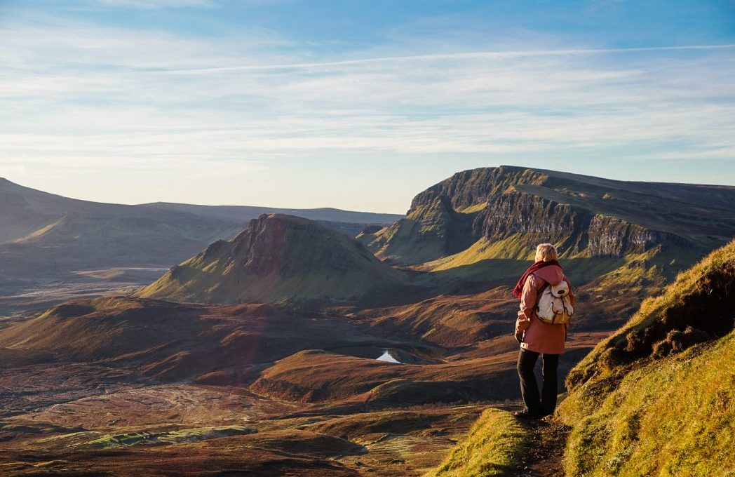 Woman standing in the hills of Scotland at sunrise.
