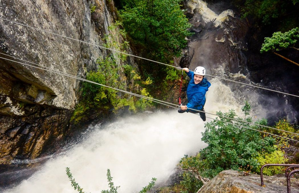 Woman on steel cables above a waterfall climbing the Via Ferrata Scotland in Kinlochleven.
