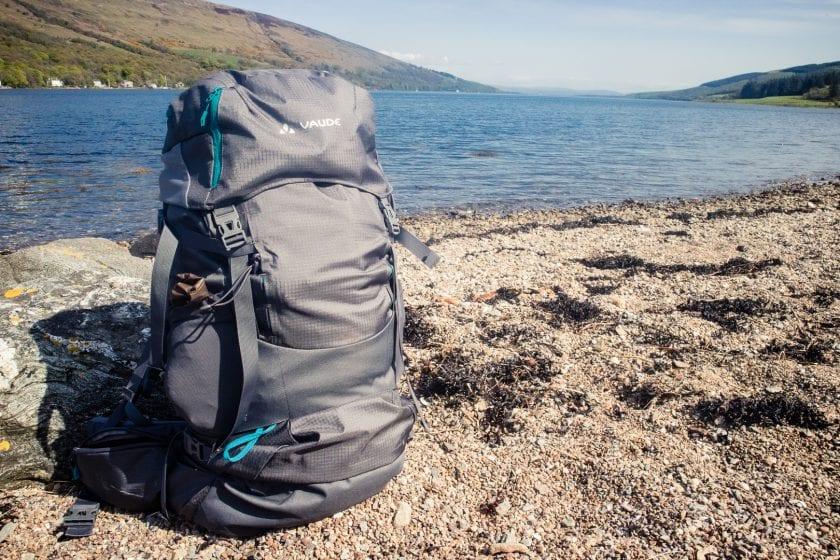 The Vaude Skarvan 65+10 trekking backpack on a beach in Scotland. - The best trekking backpacks & their must-have features