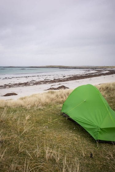 A green tent pitched on a beach.