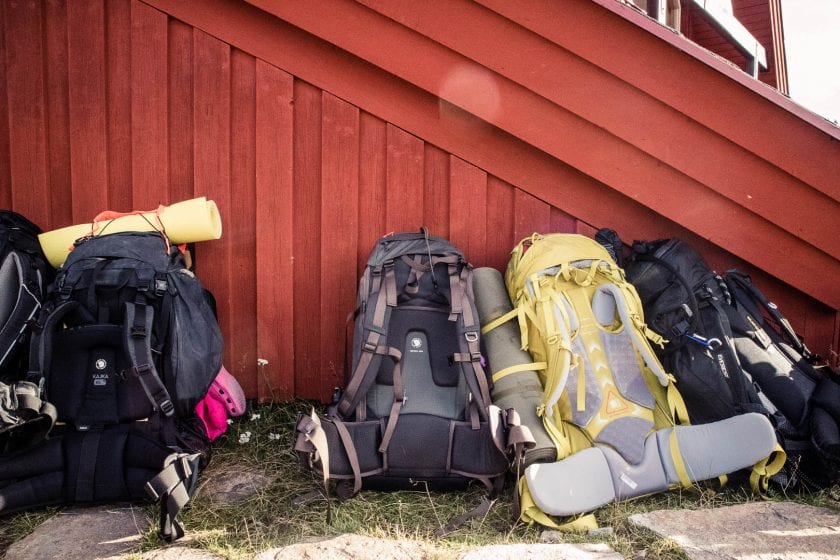 Backpacks in front of a red wall in Sweden. - The best trekking backpacks & their must-have features